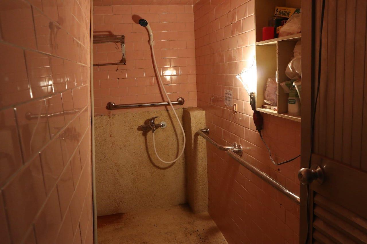 修繕後的浴室,地面改為防滑抿石子地、更換淋浴龍頭,壁面新增扶手